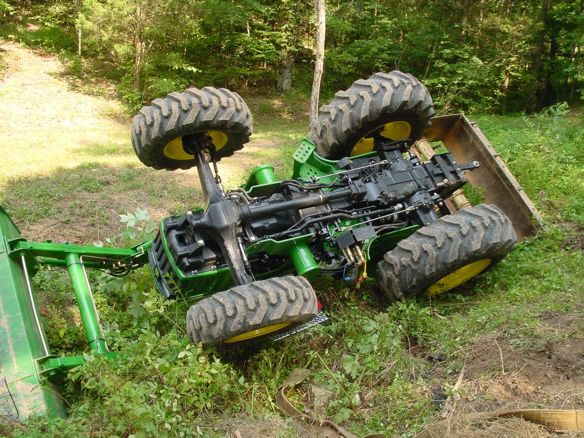 Green tractor upside down in a ditch