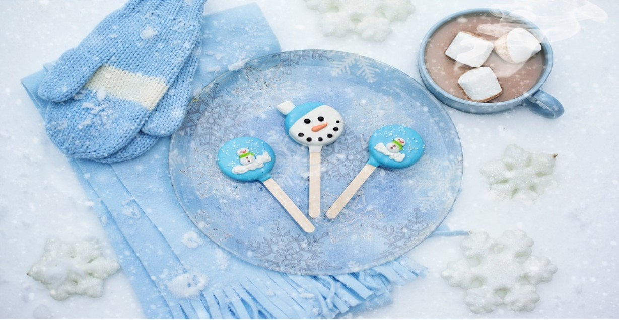 Blue plate with snowman and stocking cap Popsicles, atop a blue scarf and blue mittens