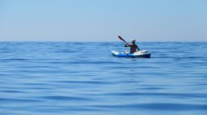 lone kayaker on blue water