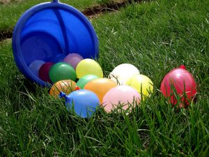 water balloons spilled out of a blue bucket onto the green grass