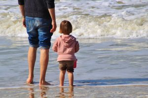 child and parent at beach father