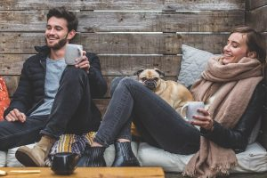 man woman drinking coffee and a pug